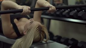 Blonde girl training at the gym. Woman engaged in fitness. Girl performing an exercise extension arms lying. triceps stock video