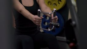 Blonde girl training at the gym. Woman engaged in fitness stock video footage