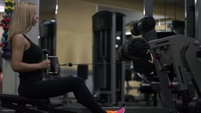 Blonde girl training at the gym. Woman engaged in fitness. Girl performs a lower block cravings for back in the simulator. trains back stock video