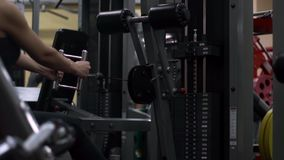 Blonde girl training at the gym. Woman engaged in fitness. Girl performs a lower block cravings for back in the simulator. trains back stock video footage