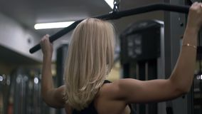 Blonde girl training at the gym. Woman engaged in fitness stock video