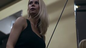 Blonde girl training at the gym. Woman engaged in fitness. Young blonde woman performing an exercise extension arms. trains the triceps stock video
