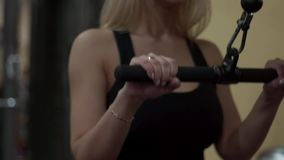 Blonde girl training at the gym. Woman engaged in fitness. Young blonde woman performing an exercise extension arms. trains the triceps stock video footage