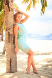 Blonde girl in transparent frock leans on palm trunk Royalty Free Stock Photos