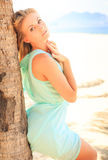Blonde girl in transparent frock leans on palm trunk Stock Photography
