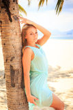 Blonde girl in transparent frock leans on palm trunk Stock Photos