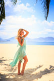 Blonde girl in transparent frock in palm shadow on beach Royalty Free Stock Image