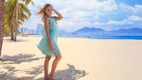 Blonde girl in transparent holds hair dress under wind on beach stock footage