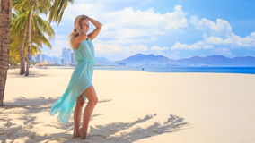 Blonde girl in transparent smoothes hair under wind on beach stock footage