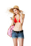 Blonde girl tuning in the right music for the beach. Isolated on white Royalty Free Stock Photos
