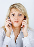 Blonde girl with two mobile phones Stock Photo