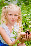 Blonde girl with two tails, sitting in the green grass with flow Royalty Free Stock Images