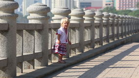 Blonde girl in Ukrainian blouse runs by barrier on embankment stock video