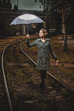 Blonde girl with umbrella balancing on rail Royalty Free Stock Images