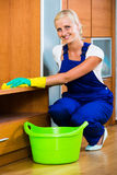Blonde girl in uniform dusting in room and smiling Stock Photos