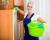 Blonde girl in uniform dusting in room and smiling stock image