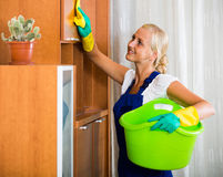 Blonde girl in uniform dusting in room and smiling royalty free stock image