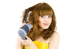 Blonde girl using hair drier Royalty Free Stock Photography