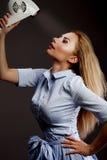Blonde girl using hair dryer. Stock Images