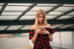 Blonde girl using phone and smiling stock photos