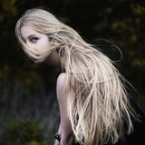 Blonde girl with very long hair on dark. Fone.Zhensky portrait. Conceptual photography. The girl`s face is covered with hair royalty free stock image