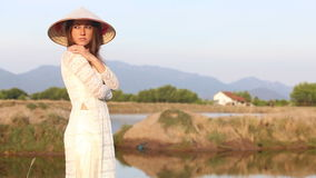 Blonde girl in vietnamese costume and hat poses near pond stock video