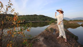Blonde girl in vietnamese costume and hat poses between ponds stock video