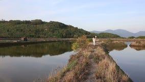Blonde girl in vietnamese costume and hat walks between ponds stock footage