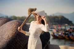 blonde girl in Vietnamese dress holds besom on embankment Royalty Free Stock Image
