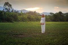 Blonde girl in Vietnamese dress holds hat on field Royalty Free Stock Photo