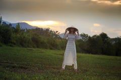 Blonde girl in Vietnamese dress lifts hat above head on field Stock Photo