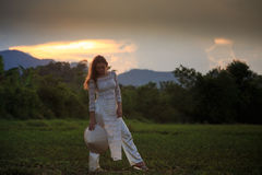 Blonde girl in Vietnamese dress looks down on field Royalty Free Stock Images