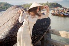 Blonde girl in Vietnamese dress pulls rope on embankment Stock Photo