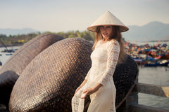 Blonde girl in Vietnamese dress touches hat by barrier Royalty Free Stock Photo