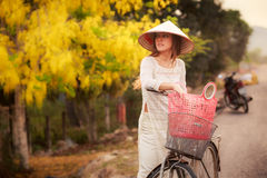 blonde girl in Vietnamese and hat by bike against yellow plant Royalty Free Stock Photography