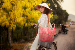 blonde girl in Vietnamese and hat by bike against yellow plant Stock Photography
