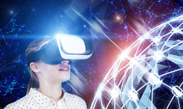 Blonde girl in VR glasses, holographic Earth Stock Photo