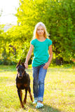Blonde girl walking with the dog or doberman in Stock Images