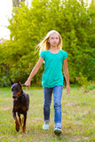 Blonde girl walking with the dog or doberman in Royalty Free Stock Image