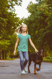 Blonde girl walking with the dog or doberman in Royalty Free Stock Images