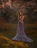 Blonde girl walking in the garden. At sunset. She wears a luxurious purple dress royalty free stock photos