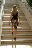 Blonde girl walking on stairs Royalty Free Stock Photos
