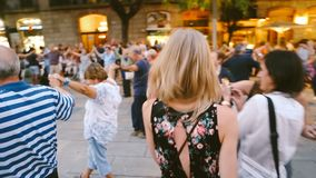 Blonde girl walks through the dancing crowd Barcelona Spain. Summer evening. Festivities. Editorial video footage. Follow me stock video