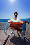Blonde girl watching the ocean on a beautiful day. Blonde female relaxing in a modern chair on a sunny day and enjoying the view to the ocean Stock Image