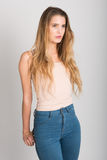 Blonde girl wearing blue jeans and t-shirt. Studio shot Stock Images