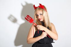 Blonde girl wearing a costume of an imp. Blonde girl wearing a red costume of an imp Royalty Free Stock Images