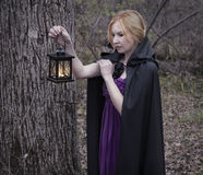 Blonde girl wearing mantle and holding lantern in the forest Royalty Free Stock Photography