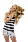 Blonde girl wearing pajamas embraces teddy bear Royalty Free Stock Photos