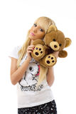 Blonde girl wearing pajamas embraces teddy bear Royalty Free Stock Photography