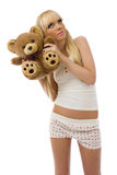 Blonde girl wearing pajamas embraces teddy bear Royalty Free Stock Photo